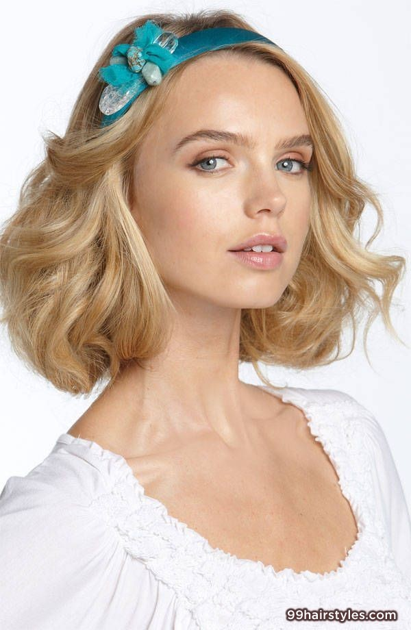 Blonde medium length wavy hairstyle with a side part and headband accessory
